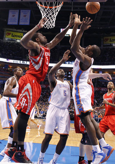 Oklahoma City 's Serge Ibaka (9) and Kendrick Perkins (5) battle under the basket with Houston's Toney Douglas (15) during the NBA basketball game between the Houston Rockets and the Oklahoma City Thunder at the Chesapeake Energy Arena on Wednesday, Nov. 28, 2012, in Oklahoma City, Okla.   Photo by Chris Landsberger, The Oklahoman