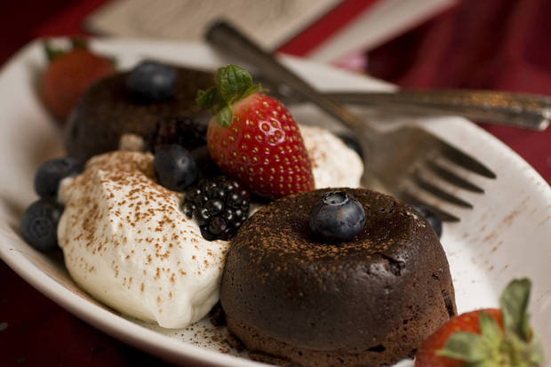 This photo taken Jan. 13, 2010 shows a flourless chocolate cake  Elegant yet easy to make this flourless chocolate cake is served with fresh whipped cream and berries. (AP Photo/Larry Crowe) ORG XMIT: NYLS126