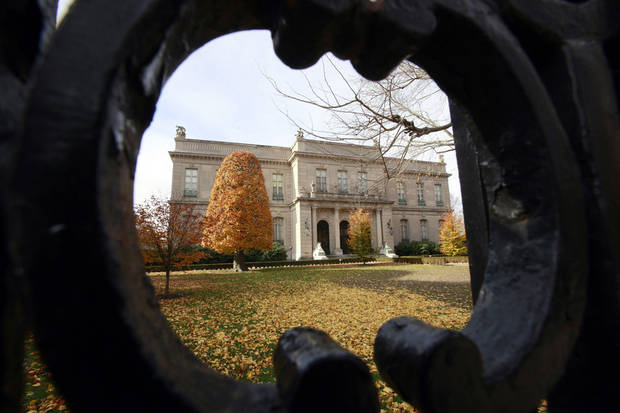 "FILE - This Nov. 19, 2010 file photo shows the Elms mansion as seen through an opening in an iron fence, in Newport, R.I.  Newly discovered photographs, documents and family histories have inspired the creation of a tour about servants at The Elms, echoing themes of the British drama program, ""Downton Abbey."" (AP Photo/Steven Senne, File)"