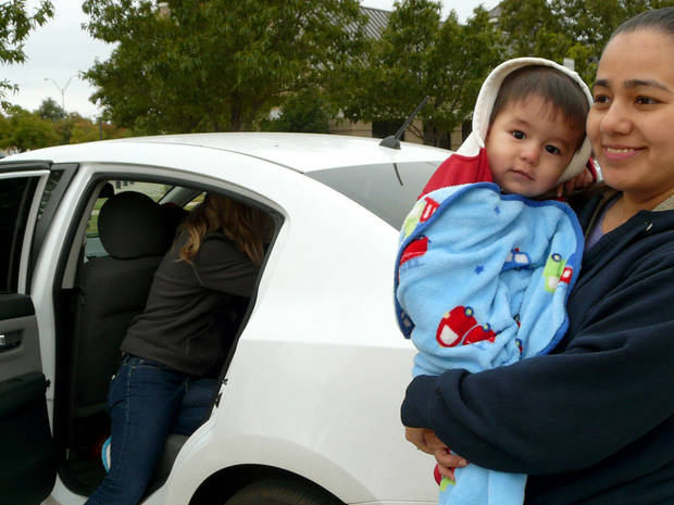 Claudia Perez holds 16-month-old son Matthew Perez Saturday while a Norman police officer checks to ensure a child safety seat is installed correctly. PHOTO BY CONNIE HEFNER, FOR THE OKLAHOMAN <strong>Connie Hefner</strong>