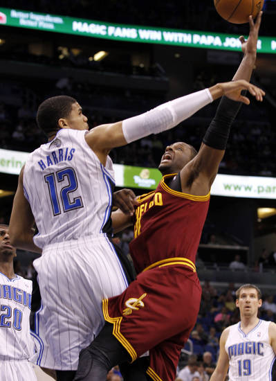 Cleveland Cavaliers guard C.J. Miles (0) shoots over Orlando Magic forward Tobias Harris (12) during the first half of an NBA basketball game in Orlando, Fla., on Saturday, Feb. 23, 2013. (AP Photo/Reinhold Matay)