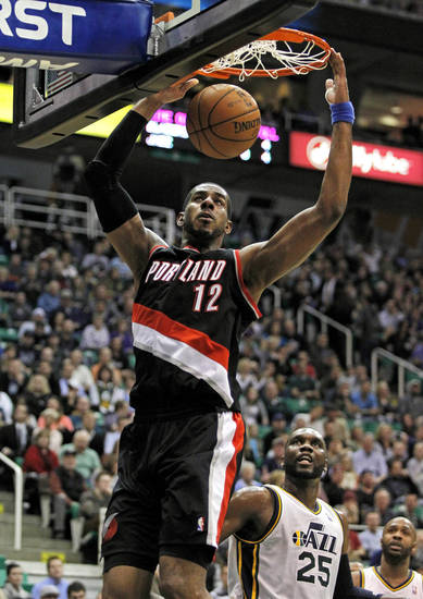 Portland Trail Blazers forward LaMarcus Aldridge (12) dunks the ball as Utah Jazz center Al Jefferson (25) looks on in the first half during an NBA basketball game on Friday, Feb. 1, 2013, in Salt Lake City. (AP Photo/Steve C. Wilson)