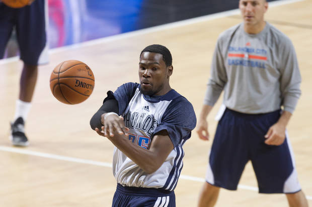 Kevin Durant passes a ball during a Oklahoma City Thunder open practice basketball session at the Phones4 u Arena in Manchester, England, Monday, Oct. 7, 2013. On Tuesday the  Thunder take on the Philadelphia 76ers as part of a series of NBA preseason games. (AP Photo/Jon Super)
