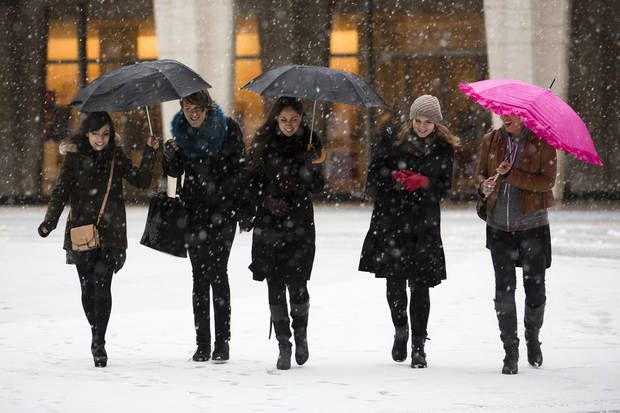 Pedestrians walk through the snow at Lincoln Center during Fashion Week, Friday, Feb. 8, 2013, in New York. Snow began falling across the Northeast on Friday, ushering in what was predicted to be a huge, possibly historic blizzard and sending residents scurrying to stock up on food and gas up their cars. (AP Photo/John Minchillo) ORG XMIT: NYJM107