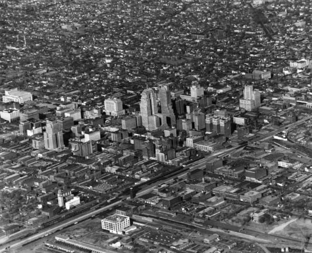 OKLAHOMA CITY / SKY LINE / OKLAHOMA / AERIAL VIEWS / AERIAL PHOTOGRAPHY / AIR VIEWS:  In 1940 - It can't happen here but here's the lovely target an enemy bomber would find approaching Oklahoma City's downtown district from the southeast.  Right ahead is the vital artery of the Santa Fe railroad tracks and then the city's tallest buildings.  The First National Bank building and, to the right, the Ramsey Tower.  Straight on the bomber would find the Belle Isle power plant and could veer west for a shot at the city's water supply, Lake Overholser.  This rare aerial view from the southwest was taken by W. E. Bleakley, veteran City aviator.  Photo taken by W. E. Bleakley.  Photo undated and published on 01/01/1940 in The Daily Oklahoman.