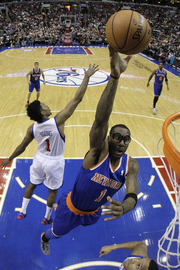 New York Knicks' Amar'e Stoudemire, right, goes up for a shot past Philadelphia 76ers' Nick Young during the first half of an NBA basketball game on Saturday, Jan. 26, 2013, in Philadelphia. (AP Photo/Matt Slocum)