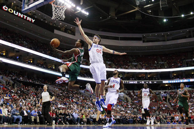 Milwaukee Bucks' Brandon Jennings, left, goes up for a shot past Philadelphia 76ers' Spencer Hawes (00) in the first half of an NBA basketball game, Monday, Nov. 12, 2012, in Philadelphia. (AP Photo/Matt Slocum)