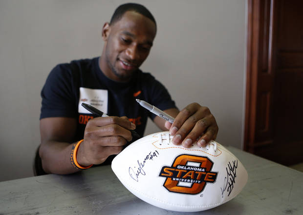 Joseph Randle signs a football during Oklahoma State's Fan Appreciation Day at Gallagher-Iba Arena in Stillwater, Okla., Saturday, Aug. 4, 2012. Photo by Sarah Phipps, The Oklahoman