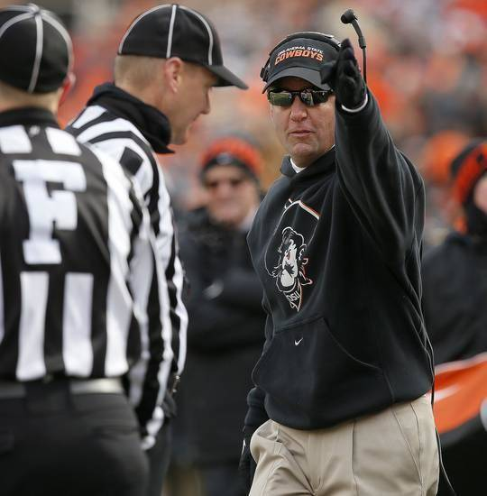 OSU coach Mike Gundy makes his case with a Big 12 official during the 2013 Bedlam game. (Photo by Bryan Terry)