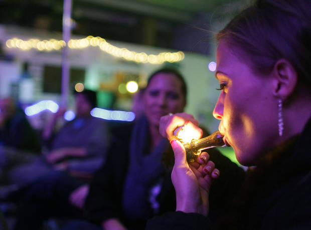 Rachel Schaefer of Denver smokes marijuana on the official opening night of Club 64, a marijuana-specific social club, where a New Year's Eve party was held, in Denver, Monday Dec. 31, 2012. On Election Day, Nov. 6, 2012, a plurality of Coloradans voted in favor of Proposition 64 to legalize recreational marijuana. (AP Photo/Brennan Linsley)