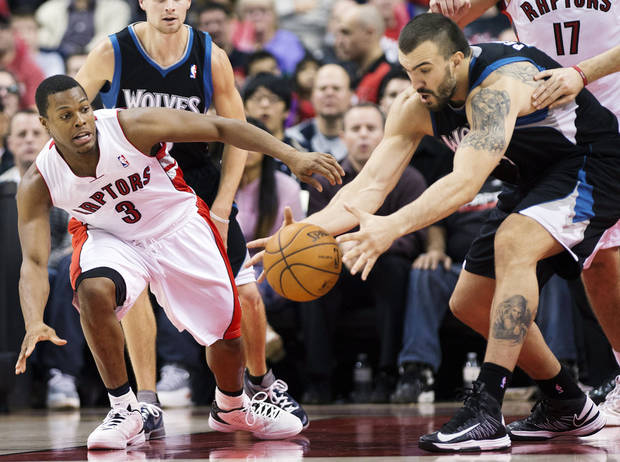 Toronto Raptors guard Kyle Lowry (3) battles for the loose ball against Minnesota Timberwolves center Nikola Pekovi, right, during the first half of their NBA basketball game, Sunday, Nov. 4, 2012, in Toronto. (AP Photo/The Canadian Press, Nathan Denette)