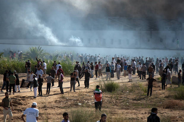 In this photo taken Friday, Sept. 14, 2012, smoke rises above protesters after they set alight cars in the U.S. embassy parking lot in Tunis. Leaked conversations in which alcohol bans and the imposition of religious law were mentioned have raised fears Tunisia�s new government may not be moderate at all, especially in the context of mob attacks on the U.S. Embassy that coincided with the American ambassador�s killing in neighboring Libya. (AP Photo/Amine Landoulsi)