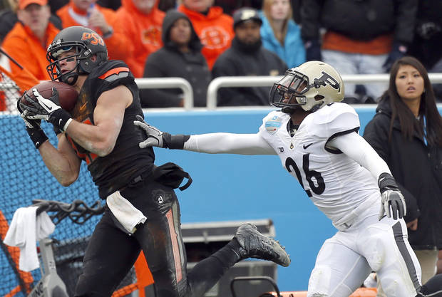 Oklahoma State&#039;s Charlie Moore (17) catches a pass in front of Purdue&#039;s Antoine Lewis during the Heart of Dallas Bowl football game between the Oklahoma State University (OSU) and Purdue University at the Cotton Bowl in Dallas,  Tuesday,Jan. 1, 2013. Photo by Sarah Phipps, The Oklahoman