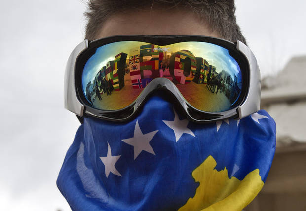 "A Kosovo Albanian youth wearing ski goggles and a Kosovo flag stands near the ""NEWBORN"" monument painted with flags of the countries that have recognized Kosovo's independence marking the 5th anniversary since Kosovo seceded from Serbia in capital Pristina on Sunday, Feb. 17, 2013. Serbia rejects Kosovo independence. (AP Photo/Visar Kryeziu)"