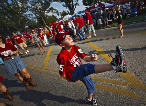 Logan Gauchat, 9, of Yukon, kicks the ball to a friend while tailgating before the college football game between the University of Oklahoma Sooners (OU) and the Tulsa University Hurricanes (TU) at the Gaylord Family-Memorial Stadium on Saturday, Sept. 3, 2011, in Norman, Okla. 