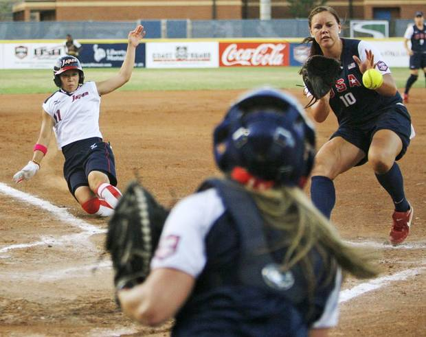 USA pitcher Keilani Ricketts (10) catches the ball tossed from catcher Ashley Holcombe (23) as Japan's Eri Yamada (11) slides home to score in the first inning during a game in the World Cup of Softball between the USA and Japan at ASA Hall of Fame Stadium in Oklahoma City, Saturday, July 23, 2011. Photo by Nate Billings, The Oklahoman ORG XMIT: KOD