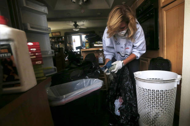 Kathleen Seemar picks up wet items from a basket as she cleans up her home, which was flooded during superstorm Sandy, Thursday, Nov. 1, 2012, in Brick, N.J. Three days after Sandy slammed the mid-Atlantic and the Northeast, New York and New Jersey struggled to get back on their feet, the U.S. death toll climbed to more than 80, and more than 4.6 million homes and businesses were still without power. (AP Photo/Julio Cortez) ORG XMIT: NJJC119