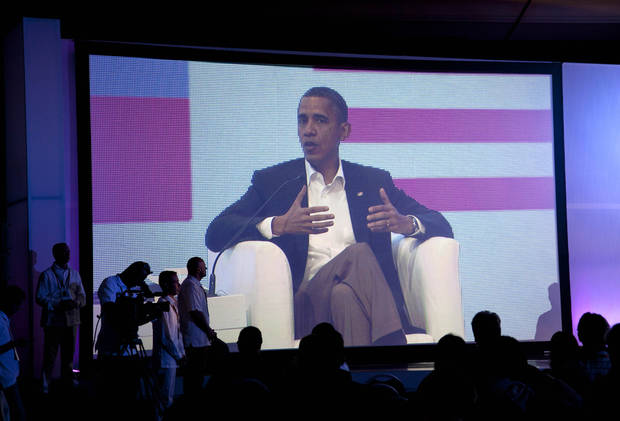 An image of President Barack Obama is displayed on a large video screen during a three-way conversation with Brazil's President Dilma Rousseff and Colombia's President Juan Manuel Santos, not pictured, at the CEO Summit of the Americas, in Cartagena, Colombia, Saturday April 14, 2012. Regional business leaders are meeting parallel to the sixth Summit of the Americas which brings together presidents and prime ministers from Canada, the Caribbean, Latin America and the U.S. (AP Photo/Carolyn Kaster)