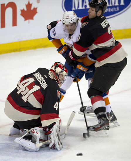 Ottawa Senators defenseman Marc Methot ties up New York Islanders center John Tavares as goalie Craig Anderson deflects a shot wide of the netd during the period of an NHL hockey game in Ottawa, Ontario, Tuesday, Feb. 19, 2013. (AP Photo/The Canadian Press, Adrian Wyld)