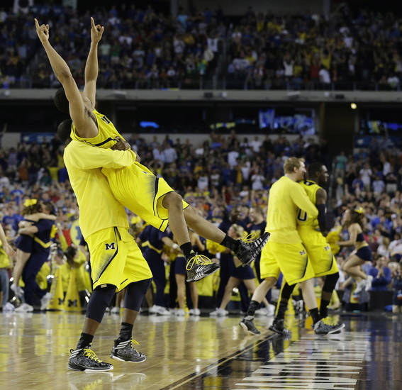 Michigan's Trey Burke, second from left, is lifted by Corey Person after beating Kansas  87-85 in overtime of a regional semifinal game in the NCAA college basketball tournament, Friday, March 29, 2013, in Arlington, Texas.(AP Photo/Tony Gutierrez)  ORG XMIT: TXKJ160