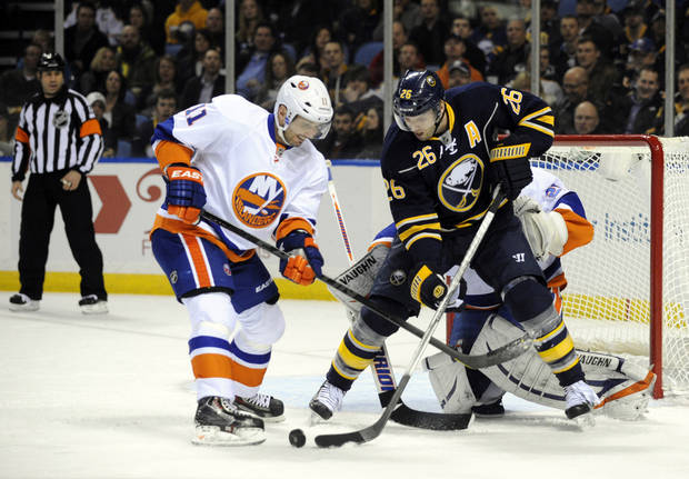 New York Islanders' defenseman Lubomir Visnovsky (11), of the Czech Republic, battles for the puck with Buffalo Sabres' left winger Thomas Vanek (26), of Austria, during the first period of an NHL hockey game in Buffalo, N.Y., Saturday, Feb. 23, 2013. (AP Photo/Gary Wiepert)