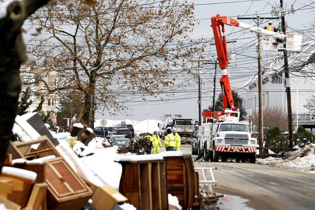 Utility workers the the power lines as snow covered debris from Superstorm Sandy lay on the side of a street following a nor'easter storm, Thursday, Nov. 8, 2012, in Point Pleasant, N.J.  The New York-New Jersey region woke up to wet snow and more power outages Thursday after the nor'easter pushed back efforts to recover from Superstorm Sandy, that left millions powerless and dozens dead last week. (AP Photo/Julio Cortez) ORG XMIT: NJJC116