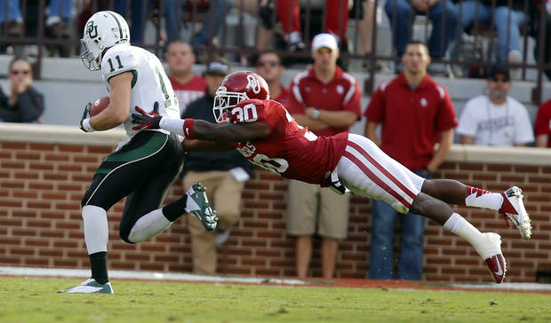 Oklahoma's Javon Harris (30) tries to stop Baylor's Nick Florence (11) during the college football game between the University of Oklahoma Sooners (OU) and Baylor University Bears (BU) at Gaylord Family - Oklahoma Memorial Stadium on Saturday, Nov. 10, 2012, in Norman, Okla.  Photo by Chris Landsberger, The Oklahoman
