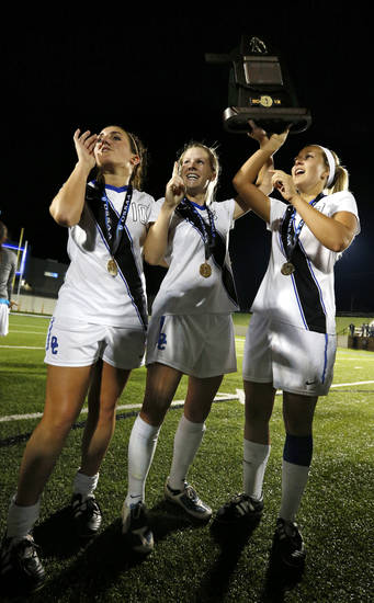 Deer Creek players Mikalyn Johnson, Rachel Landes, and Sophia Brazil hoist the championship trophy after the Class 5A girls state soccer championship game between Deer Creek and Carl Albert on Friday, May 10, 2013 in Noble, Okla.  Photo by Steve Sisney, The Oklahoman