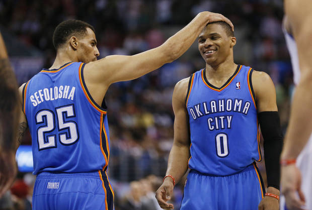 Oklahoma City Thunder guard Thabo Sefolosha, left, puts his hand on the head of guard Russell Westbrook, right, after Westbrook made one of two free throws late in the fourth quarter against the Los Angeles Clippers during the first half of an NBA basketball game in Los Angeles, Wednesday, April 9, 2014. The Thunder won 107-101. (AP Photo/Danny Moloshok)