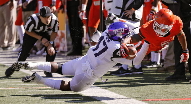 Oklahoma State's Josh Stewart (5) is forced out of bounds on a catch by TCU's Paul Dawson (47) during a college football game between the Oklahoma State University Cowboys (OSU) and the Texas Christian University Horned Frogs (TCU) at Boone Pickens Stadium in Stillwater, Okla., Saturday, Oct. 19, 2013. Photo by Chris Landsberger, The Oklahoman