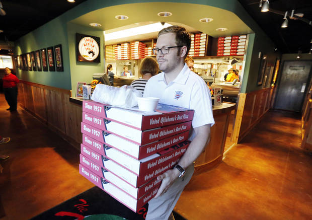 Hideaway Pizza customer Ben Coldagelli carries a take-out order at the restaurant on North Western Avenue in Oklahoma City. The restaurant, shuttered by fire a year ago, reopened Monday. <strong>Steve Gooch - The Oklahoman</strong>