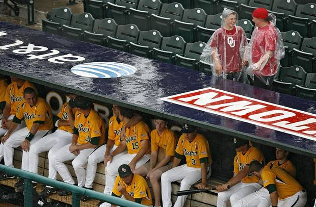 Sooner baseball fans brave the rain over the Baylor dugout in the rain delay during the third game of the Big 12 Baseball Championship between Kansas State and Baylor at the Bricktown Ballpark on Wednesday, May 26, 2010, in Oklahoma City, Okla.  Photo by Chris Landsberger, The Oklahoman