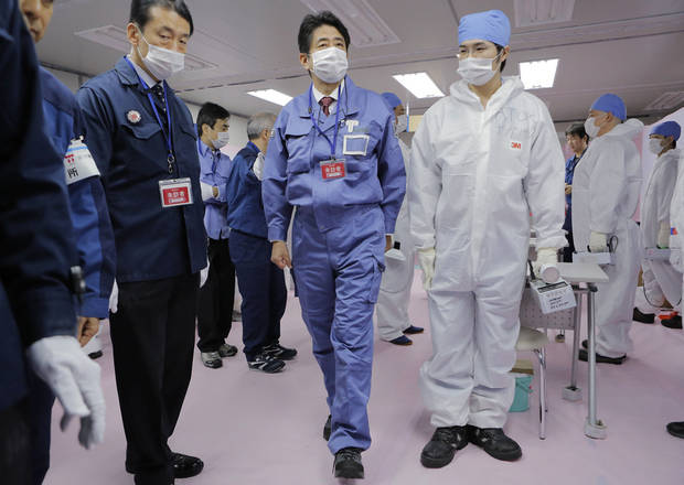 Japan's new Prime Minister Shinzo Abe, center, inspects the emergency operation center of the Tokyo Electric Power Co.(TEPCO)  at the crippled Fukushima Dai-ichi nuclear power plant in Okuma, Fukushima prefecture, northeastern Japan, Saturday, Dec. 29, 2012. Abe's visit Saturday to the plant comes amid pledges from his ruling Liberal Democratic Party to review the country's plans to phase out nuclear power. (AP Photo/Itsuo Inouye, Pool)