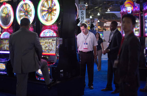 Casino industry professionals browse through the newest slot machines on display at the Global Gaming Expo, Tuesday, Oct. 2, 2012, in Las Vegas. Casino revenues have increased this year in 18 of the 21 states that allow commercial gambling and, new casinos are opening in several jurisdictions. (AP Photo/Julie Jacobson)
