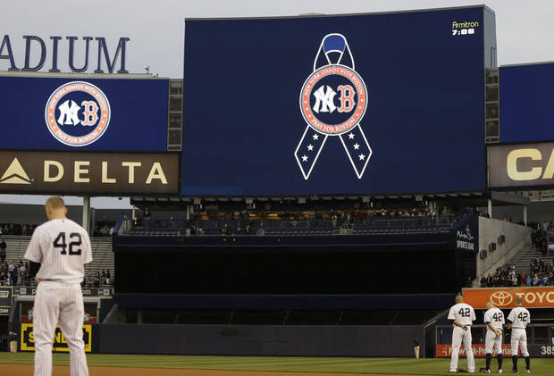 New York Yankees players observe a moment of silence in memory of the victims of the Boston Marathon explosions before a baseball game against the Arizona Diamondbacks at Yankee Stadium in New York, Tuesday, April 16, 2013. (AP Photo/Kathy Willens)