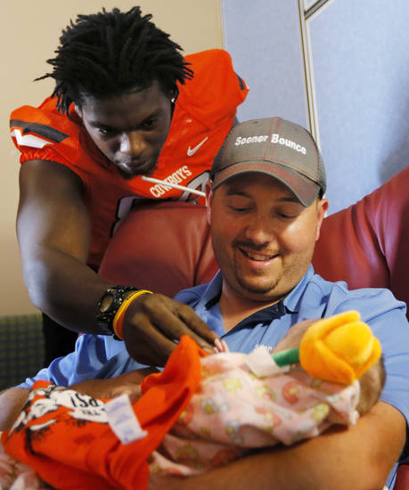 Oklahoma State's Nigel Nicholas touches the hand of 9-week-old Libbye Marshall as she is held by her father, Juston Marshall, during a visit by OSU football players to The Children's Hospital in Oklahoma City, Wednesday, July 11, 2012. Libbye Marshall is a patient at The Children's Hospital. Photo by Nate Billings, The Oklahoman