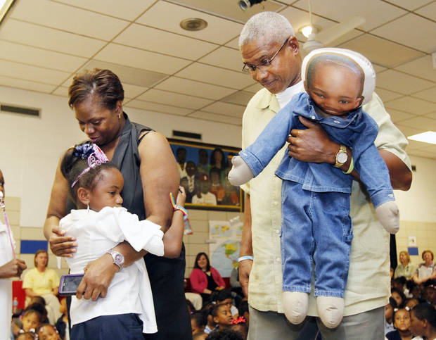 Abria Glenn is embraced by her parents, Gregory and Anbria Glenn, after being surprised with her Make-A-Wish Foundation trip to Walt Disney World Resort during an assembly at Stanley Hupfeld Academy in Oklahoma City. Her father is holding a doll made in her late brother Gregory Dwayne�s likeness.  Photo by PAUL HELLSTERN, The Oklahoman