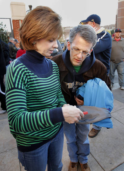 Notre Dame fans Alice and Curt Rohrman look at pictures they made of their team's arrival before the college football game between the University of Oklahoma Sooners (OU) and the Fighting Irish of Notre Dame (ND) at Gaylord Family-Oklahoma Memorial Stadium in Norman, Okla., on Saturday, Oct. 27, 2012. The Rohrmans are from Houston, but their daughter is a Notre Dame student.  Photo by Steve Sisney, The Oklahoman
