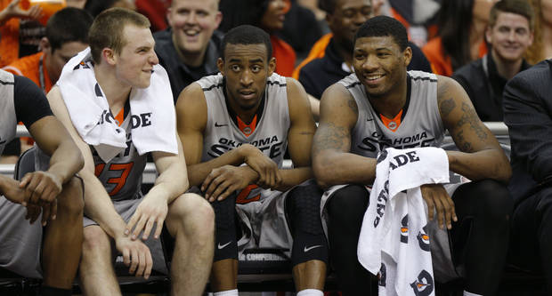 Oklahoma State's Phil Forte (13), Markel Brown (22), and Marcus Smart (33) sit on the bench in the final minutes of their Big 12 tournament college basketball game between Oklahoma State University and Texas Tech at the Sprint Center in Kansas City, Mo., Wednesday, March 12, 2014. Oklahoma State won 80-62. Photo by Bryan Terry, The Oklahoman