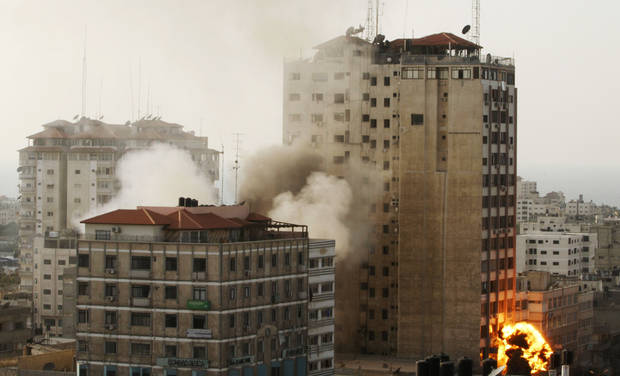 Smoke and fire are seen from an explosion by a high rise housing media organizations in Gaza City, Monday, Nov. 19, 2012. It's the Israel's military second strike on the building in two days. The Hamas TV station, Al Aqsa, is located on the top floor. (AP Photo/Hatem Moussa)