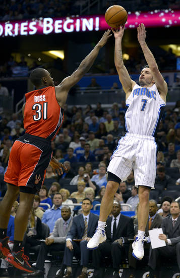 Orlando Magic guard J.J. Redick (7) puts up a shot in front of Toronto Raptors guard Terrence Ross (31) during the first half of an NBA basketball game in Orlando, Fla., Saturday, Dec. 29, 2012. (AP Photo/Phelan M. Ebenhack)