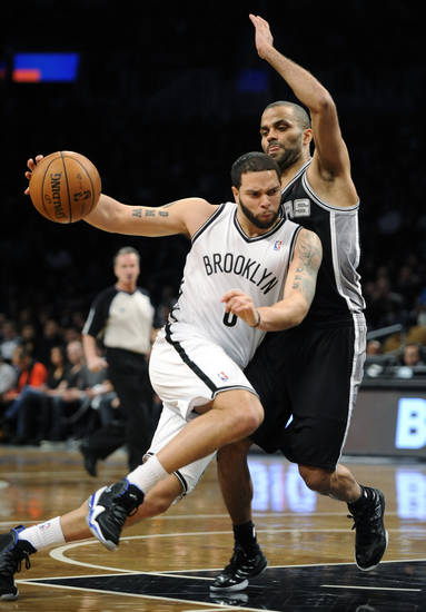 Brooklyn Nets' Deron Williams (8) drives the ball around San Antonio Spur's Tony Parker in the first half of an NBA basketball game, Sunday, Feb. 10, 2013, at Barclays Center in New York. (AP Photo/Kathy Kmonicek)