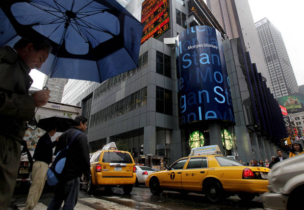 In this Wednesday, Oct. 10, 2012 photo, people pass Morgan Stanley's headquarters in New York. Morgan Stanley says it swung to a profit in the fourth quarter. Shares jumped in pre-market trading, Friday, Jan. 18, 2013. (AP Photo/Richard Drew)