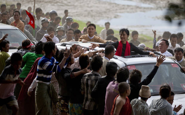 Supporters of opposition leader Aung San Suu Kyi reach to touch her hand as she leaves after a public meeting close to Letpadaung mine in Monywa, northwestern Myanmar, Friday, Nov. 30, 2012. Suu Kyi is urging a negotiated resolution to protests over a military-backed copper mine in northwestern Myanmar after the government's biggest crackdown on demonstrators since reformist President Thein Sein took office last year. (AP Photo/Gemunu Amarasinghe)