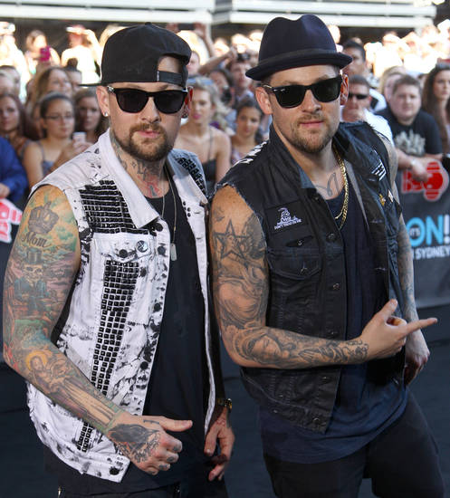 American rocker brothers Joel, right, and Benji Madden pose for photographers upon arrival for the Australian music industry Aria Awards in Sydney, Thursday, Nov. 29, 2012. (AP Photo/Rick Rycroft)