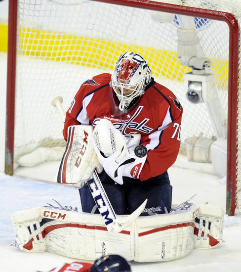 Washington Capitals goalie Braden Holtby (70) deflects the puck during the third period of an NHL hockey game against the Boston Bruins, Saturday, April 27, 2013, in Washington. The Capitals won 3-2 in overtime. (AP Photo/Nick Wass)