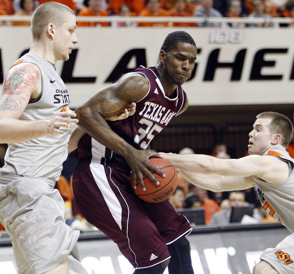 Texas A&M's Ray Turner (35) tries to get past the defense of OSU's Philip Jurick (44), left, and Keiton Page (12) in the second half of a men's college basketball game between the Oklahoma State University Cowboys and Texas A&M University Aggies at Gallagher-Iba Arena in Stillwater, Okla., Saturday, Feb. 25, 2012. OSU won, 60-42. Photo by Nate Billings, The Oklahoman