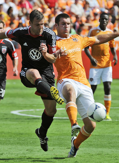 D.C. United's Daniel Woolard, left, and Houston Dynamo's Will Bruin battle for possession of the ball in the first half of an MLS soccer match, Saturday, May 12, 2012, in Houston. (AP Photo/Pat Sullivan)