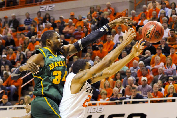 Baylor forward Cory Jefferson, left, reaches over Oklahoma State forward Michael Cobbins for a rebound during the first half of an NCAA college basketball game in Stillwater, Okla., Wednesday, Feb. 6, 2013. (AP Photo/Brody Schmidt)
