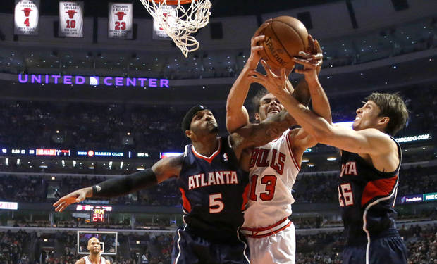 Chicago Bulls' Joakim Noah (13) struggles with Atlanta Hawks' Josh Smith and Kyle Korver (26) for a rebound during the first half of an NBA basketball game Monday, Jan. 14, 2013, in Chicago. (AP Photo/Charles Rex Arbogast)